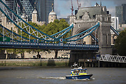 A met police launch boat in the waters of the River Thames beneath the Victorian-era Tower Bridge with the Norman Tower of London in the capitals financial district aka The Square Mile behind, on 5th October, 2017, in London, England. The Gabriel Franks is a Fast Response Targa 31 boat of the Metropolitan Police Marine Policing Unit, named after the first British marine police officer to be killed in the line of duty.