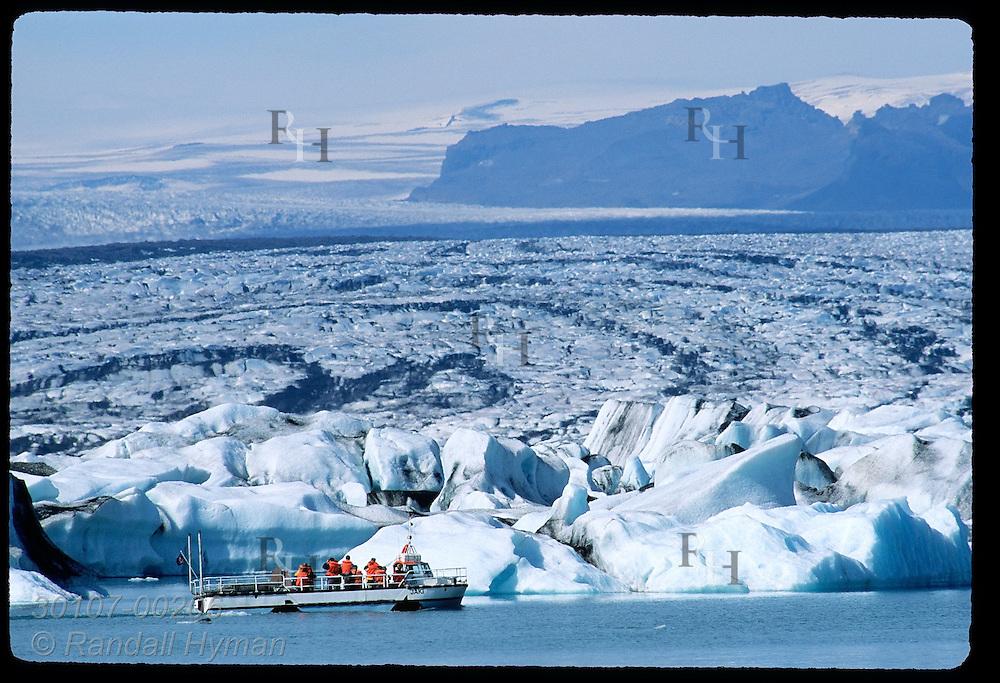 Amphibious boat glides past Breidamerkurjokull glacier in Jokulsarlon (Glacier Lagoon) on a summer sightseeing trip; SE Iceland.