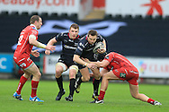 Dan Biggar of the Ospreys (c)  ,on as a replacement, tries to set up an attack but is stopped by James Davies of the Scarlets (r). Guinness Pro12 rugby match, Ospreys v Scarlets at the Liberty Stadium in Swansea, South Wales on Saturday 26th March 2016.<br /> pic by  Andrew Orchard, Andrew Orchard sports photography.