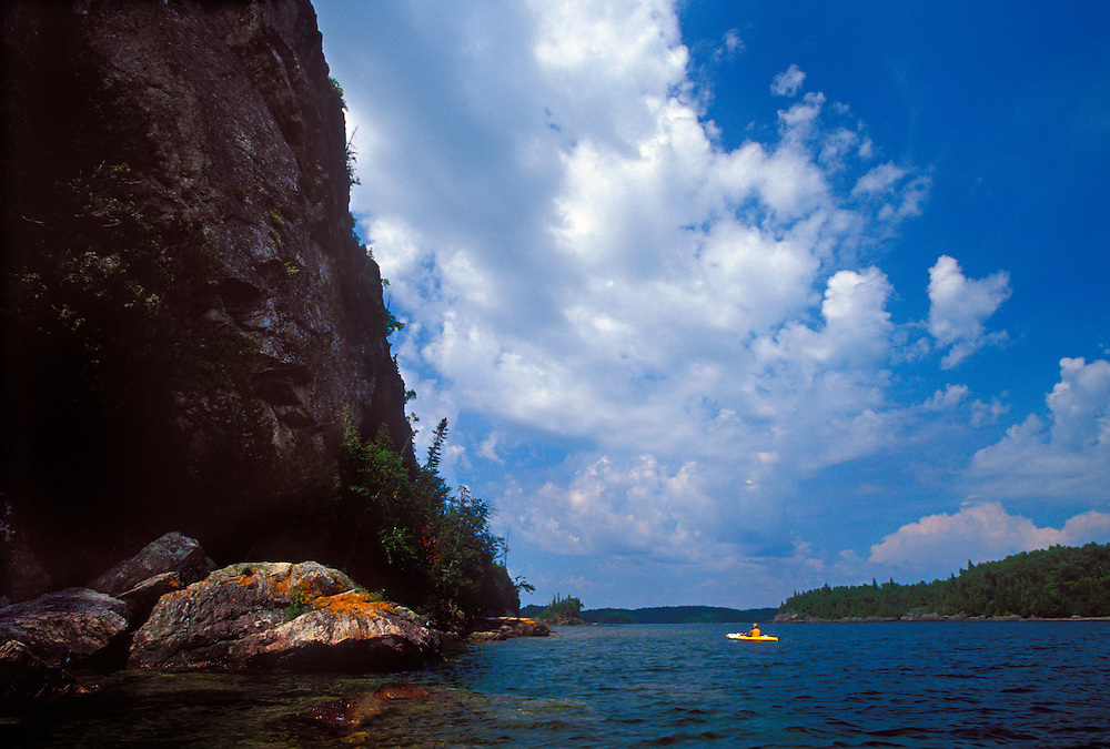 A sea kayaker is dwarfed by a cliff on on Devil's Warehouse Island and an open sky at Lake Superior Provincial Park near Wawa, Ontario.