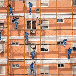 Trabalhadores a pintarem o prédio Rainha Ginga (SICCAL) em Luanda, Angola.
