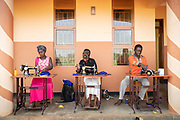 Portrait of two women and man sewing at Design and Tailoring Centre, Musoto, Uganda