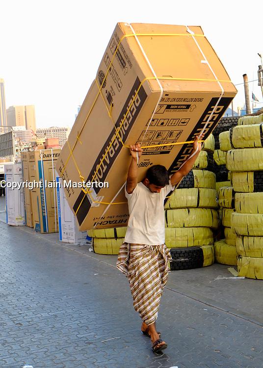 Loading cargo onto dhow onn  Creek river in Dubai United Arab Emirates UAE