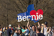 "Brooklyn, NY - 17 April 2016. A man holds a large painted sign in the shape of a blue map of the state of New York, with a large red heart superimposed on it, and the word ""Berie."" Vermont Senator Bernie Sanders, who is running as a Democrat in the U.S. Presidential primary elections, held a campaign ""get out the  vote"" rally in Brooklyn's Prospect Park."