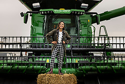© Licensed to London News Pictures. 12/07/2021. Harrogate UK. TV presenter poses in the rain in front of a state of the art John Deere X9 1100 which is the largest & most technologically advanced combine harvester in the world ahead of the 162nd Great Yorkshire Show which starts tomorrow in Harrogate, Yorkshire. Photo credit: Andrew McCaren/LNP