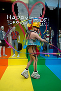 Pride in London, formally known as Pride London, is an annual LGBT pride festival and parade held each summer in London, United Kingdom. Top Shop window with Loveheart and Happy Pride. A bearded man in shorts dances with a rainbow coloured ribbon.