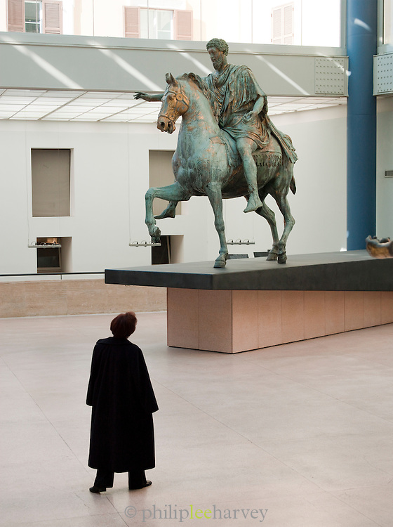Tourist looking at the oringinal Statue of Marcus Aurelius from Capitoline Hill in the Capitoline Museum, Rome, Italy