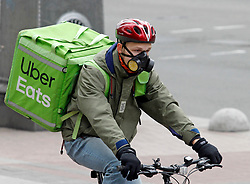 March 17, 2020, Kiev, Ukraine: Uber Eats food delivery man wearing a protective mask rides on a bike in Kiev. Ukraine suspend all air, rail and bus services between cities and regions of Ukraine from March 18th and closure the subway in cities from March 17th, as quarantine measures against the spread the COVID-19 coronavirus. (Credit Image: © Serg Glovny/ZUMA Wire)