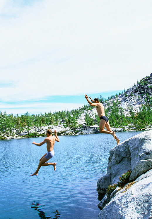 Two men jumping into an alpine lake in their underwear.
