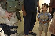 A young Iraqi holds suckers his father has allowed him to have as he looks up to Maj. Phil Williams, 39, of Gadsden, Ala., in a neighborhood of Baghdad Saturday, Oct. 2, 2004. Williams is the civil affairs officer  for Second Battalion, 162nd Infantry of the Oregon National Guard. He and other members of the guard were walking through the streets, talking with people and handing out candy, soccer balls, shoes, shirts and backpacks.  <br /> Photo by Randy L. Rasmussen/The Oregonian