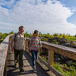 A couple hikes over a bridge near the summit of Mount Agamenticus in York, Maine.