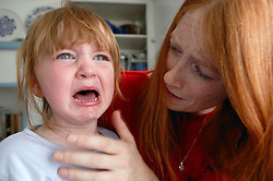 Stressed Mother with tearful young girl,
