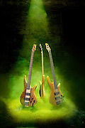 Three floating Ibanez electric bass guitars in a mysterious beam of green fog that swirls around the guitars. A surreal scene of bass guitars levitating in the air.