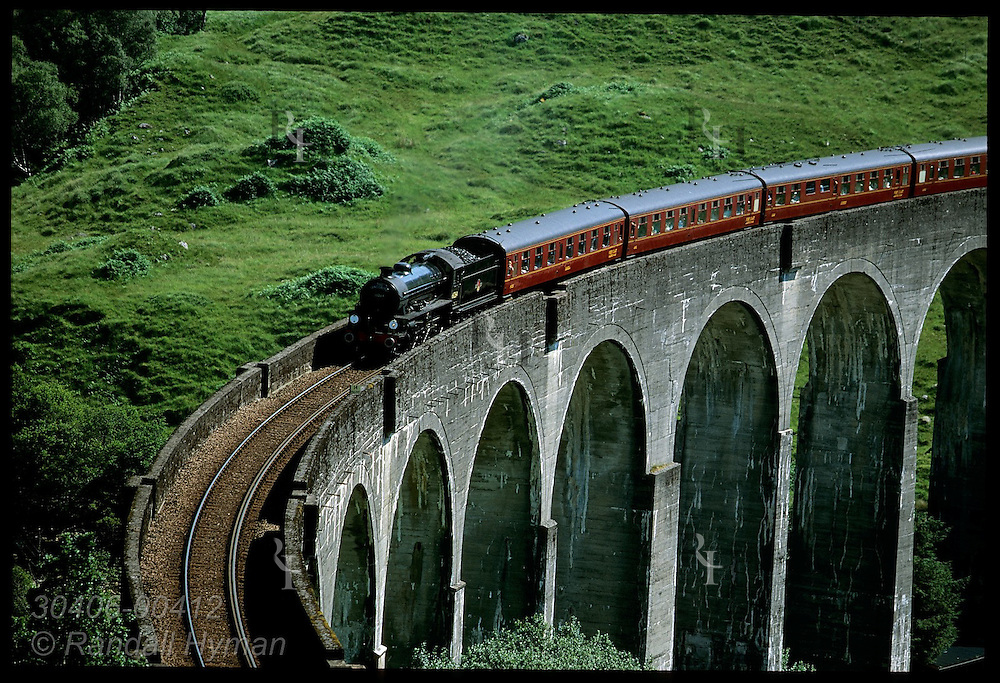 Jacobite Steam Train crosses Glenfinnan Viaduct, 100'-tall, 21-arch concrete marvel (built 1901) seen in Harry Potter films; Scotland.