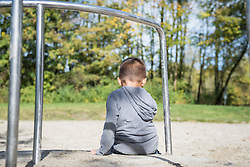 Small lonely boy sitting alone in playground