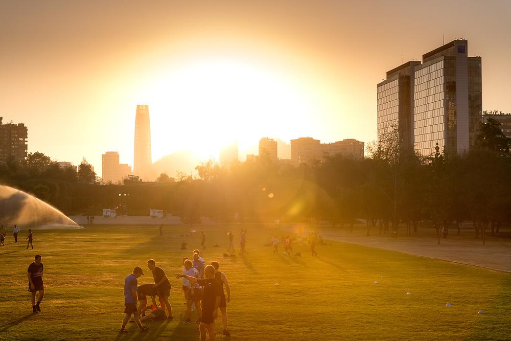 Santiago, Region Metropolitana, Chile - People practicing sports at Parque Araucano, the main park in Las Condes district, surrounded by office buildings of Nueva Las Condes business center.