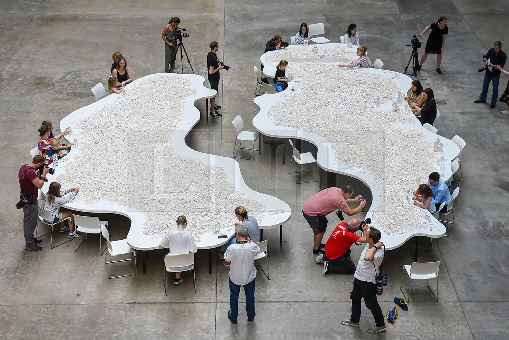 """© Licensed to London News Pictures. 26/07/2019. LONDON, UK.  Preview of """"The cubic structural evolution project"""", 2004, by Olafur Eliasson at Tate Modern.  Exhibited for the first time in the UK, the artwork comprises one tonne of white Lego bricks inspiring visitors to create their own architectural vision for a future city and is on display until 18 August 2019.  The work coincides with the artist's new retrospective exhibition """"In real life"""" at Tate Modern on display to 5 January 2020.  Photo credit: Stephen Chung/LNP"""