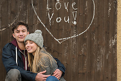 Young couple hugging with a drawn heart and love you written on a wooden wall, Munich, Bavaria, Germany