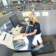 8/29/08 Omaha, NEB.Among a sea of cubicles, Zandra Hooks, clicks her mouse and talks on the phone all while walking on a treadmill Friday morning..Mutual of Omaha has 4 Walkstations in their customer-service area. Workers spend part of their shift walking on a treadmill while answering calls..Chris Machian/For the NY TImes..CONTACT INFO FOR Zandra Hooks.402 202 0870