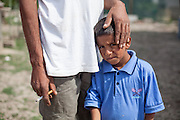 A Roma father holding the head of his son in the Roma area of Frumusani.