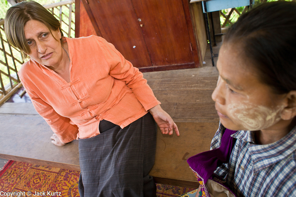 """19 FEBRUARY 2008 -- SANGKLABURI, KANCHANABURI, THAILAND: DIDI DEVAMALA, founder of Baan Unrak Children's Home, interviews AYEA MU, a Burmese Karen refugee woman, about children. Ayea said she was sick, very poor and no longer able to care for either her infant or twins so she was hoping to leave them at Baan Unrak. Devamala tried to convince her to keep the children and accept help from the home. She said the home's first goal was always to keep families together. Baan Unrak children's home and school, established in 1991 in Sangklaburi, Thailand, gives destitute children and mothers a home and career training for a better future. Baan Unrak, the """"Home of Joy,"""" provides basic needs to well over 100 children, and  abandoned mothers. The home is funded by donations and the proceeds from the weaving and sewing shops at the home. The home is a few kilometers from the Burmese border. All of the women and children at the home are refugees from political violence and extreme poverty in Burma, most are Karen hill tribe people, the others are Mon hill tribe people. The home was started in 1991 when Didi Devamala went to Sangklaburi to start an agricultural project. An abandoned wife asked Devmala to help her take care of her child. Devmala took the child in and soon other Burmese women approached her looking for help.    Photo by Jack Kurtz"""