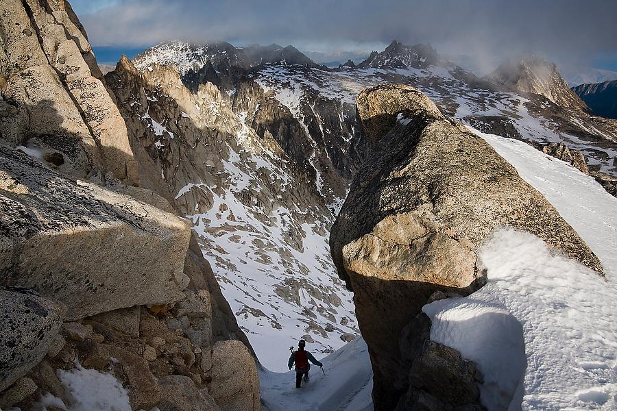 Climber Grace Marx descends a narrow snow couloir below the summit of Dragontail Peak, Alpine Lakes Wilderness, Washington.
