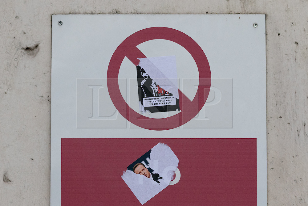 """© Licensed to London News Pictures. 30/12/2015. London, UK. A """"No hipster, No Yuppies, No gentrification, get the fuck out"""" sticker on the outside of the Royal Mint building. Squatters have occupied the former Royal Mint building, located opposite the Tower of London on the border of the City of London to protest against homelessness and highlight how empty buildings could provide shelter for rough sleepers. The site was previously used to manufacture British coins but is currently vacant and activists argue that this along with other vacant commercial buildings could be used to provide short term shelter for the homeless. Photo credit : Vickie Flores/LNP"""