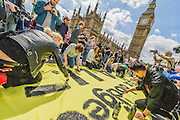 A protest organised by UK Uncut marches from Waterloo Station towards Parliamentwhere a large banner is painted on Westminster Bridge. It is then lowered over the side of the bridge weighted down by milk cartons. Eventually the Police force its removal to the embankment in front of St Thomas' Hospital. The banner read - 312bn more cuts, £120hn tax dodged, AUSTERITY IS A LIE - which sums up what they were protesting about.
