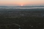 Mandalay, Myanmar - November 8 2011: The setting sun is viewed from Mandalay Hill, setting beyond the city of Mandalay and the Ayeyarwady River