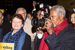"""London, October 23 2017. Nelson Mandela's group of Elders including former UN Secretary General Kofi Annan and Secretary General Ban Ki-moon accompanied by his widow Graca Machel gather at Parliament Square at the start of the Walk Together event in memory of Nelson Mandela before a candlelight vigil at his statue in Parliament Square. """"WalkTogether is a global campaign to inspire hope and compassion, celebrating communities working for the freedoms that unite us"""". PICTURED: A mischievous Kofi Annan borrows a press photographer's camera. © Paul Davey"""