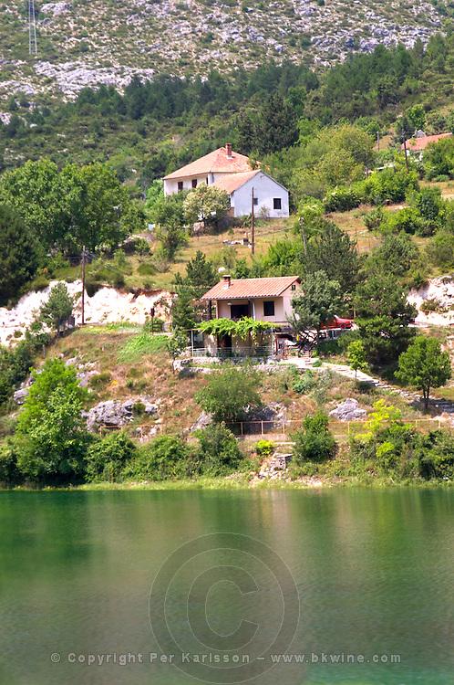 View of the river Trebisnjica in a steep valley near Trebinje. Small houses along the river. Trebinje. Republika Srpska. Bosnia Herzegovina, Europe.