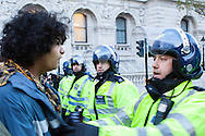 A student protesting against student fees confronts a police officer in a demonstration in London
