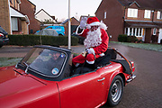Santa Clause travelling around a housing estate at dawn on a winter morning in a red sports car in Olney, England, United Kingdom. (photo by Mike Kemp/In Pictures via Getty Images)