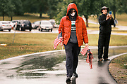 10 SEPTEMBER 2020 - DES MOINES, IOWA: A volunteer carrying American flags walks on the path along Gray's Lake. About 25 volunteers braved cold and rainy weather Thursday to line the west end of Gray's Lake in Des Moines with American flags. The display of flags was a part of an annual event called the 9/11 Tribute Trail. About 3,000 flags were set out in memorial of the 3,000 people killed in the 9/11 terrorist attacks.     PHOTO BY JACK KURTZ