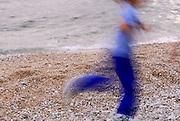 Child running on pebble beach, motion-blurred. Makarska, Croatia