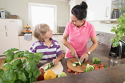 Woman with her son chopping vegetables in kitchen, Bavaria, Germany
