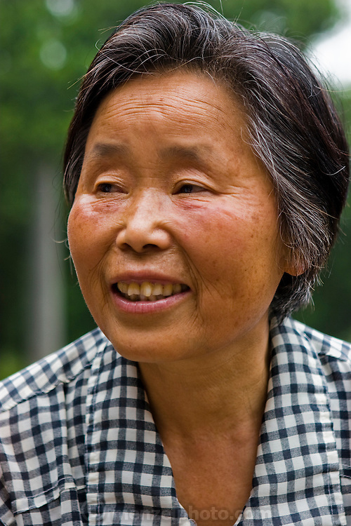 Lan Guihua, a widowed farmer, at her home in Ganjiagou Village, Sichuan Province, China. (Lan Guihua is featured in the book What I Eat: Around the World in 80 Diets. The caloric value of her day's worth of food on a typical day in June was 1900 kcals. She is 68 years of age; 5 feet, 3 inches tall; and 121 pounds. Her farmhouse is tucked into a bamboo-forested hillside beneath her husband's grave, and the courtyard opens onto a view of citrus groves and vegetable fields. Chickens and dogs roam freely in the packed-earth courtyard, and firewood and brush for her kitchen wok are stacked under the eaves. Although homegrown vegetables and rice are her staples, chicken feathers and a bowl that held scalding water for easier feather plucking are clues to the meat course of a special meal for visitors. In this region, each rural family is its own little food factory and benefits from thousands of years of agricultural knowledge passed down from generation to generation.  She lives in the area of Production Team 7 of Ganjiagou Village, 1.5 hours south of the provincial capital of Sichuan Province?Chengdu. MODEL RELEASED.