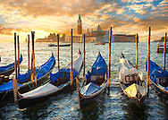 Sunset view of gondolas at St Mark's Square with the island of San Giorgio Maggiore behind , with its church front designed by Andrea Palladio and begun in 1566.  Venice Italy . The gondola ( góndoła ) is a traditional, flat-bottomed Venetian rowing boat, well suited to the conditions of the Venetian lagoon.  gondolas are typically propelled by a gondolier, who uses a rowing oar, which is not fastened to the hull, in a sculling manner and also acts as the rudder. The oar of the  gondola rests in an elaborately carved wooden rest (forcola) shaped to project from the side of the craft so as to allow the slight drag of each return stroke to pull the bow back to its forward course. For centuries, the gondola was a major means of transportation and the most common watercraft within Venice. .<br /> <br /> Visit our ITALY HISTORIC PLACES PHOTO COLLECTION for more   photos of Italy to download or buy as prints https://funkystock.photoshelter.com/gallery-collection/2b-Pictures-Images-of-Italy-Photos-of-Italian-Historic-Landmark-Sites/C0000qxA2zGFjd_k