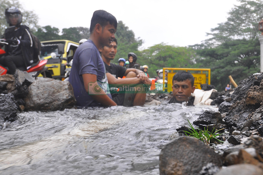 April 14, 2018 - Bogor, West Java, Indonesia - The water leak from pipe on jalan Harupat, Sempur, Bogor made some operators from Local Water Supply Utility busy. Because the leak was near Bogor Presidential Palace and the road is usually used by the President. Not only made a long traffic jam, this leak is also used  by some people to wash their motorcycle. (Credit Image: © Andi Muh Ridwan/Pacific Press via ZUMA Wire)
