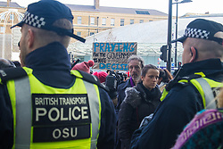 """St Pancras, London, January 16th 2016. Dozens of protesters hold an """"emergency demonstration and die-in"""" as France prepares to bulldoze the Jungle Camp at Calais. PICTURED: Bemused travelers make their way into the St Pancras Eurostar terminal, through the protest and police lines blocking entry to the demonstrators. ///FOR LICENCING CONTACT: paul@pauldaveycreative.co.uk TEL:+44 (0) 7966 016 296 or +44 (0) 20 8969 6875. ©2016 Paul R Davey. All rights reserved."""