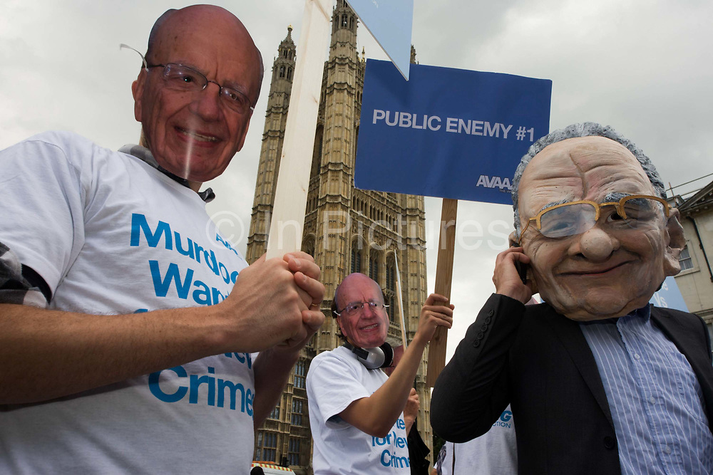 "Politcal action group Avaaz wear Rupert Murdoch masks outside Parliament during News International phone hacking scandals. As the News International Chairman and his son sit  inside the committee rooms answering difficult questions about the phone hacking scandals, the activists protest outside. Avaaz—meaning ""voice"" in several European, Middle Eastern and Asian languages—launched in 2007 with a simple democratic mission: organize citizens of all nations to close the gap between the world we have and the world most people everywhere want."