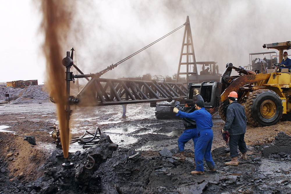 """Firefighters from the KWWK (Kuwait Wild Well Killers) attempt to kill an oil fire in the Rumaila field by guiding a """"stinger"""" that will pump drilling mud into the damaged well. A """"stinger"""" is a tapered pipe on the end of a long steel boom controlled by a bulldozer. Drilling mud, under high pressure, is pumped through the stinger into the well, stopping the flow of oil and gas. A sudden wind shift after a sandstorm caused the oil to blow back on the workers and equipment, causing a very dangerous situation because the oil and gas could have easily ignited. The Rumaila field is one of Iraq's biggest oil fields with five billion barrels in reserve. Many of the wells are 10,000 feet deep and produce huge volumes of oil and gas under tremendous pressure, which makes capping them very difficult and dangerous. This well is of relatively low volume. Rumaila is also spelled Rumeilah.."""