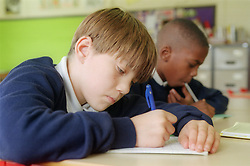 Two secondary school teenage boys writing at desk in classroom,