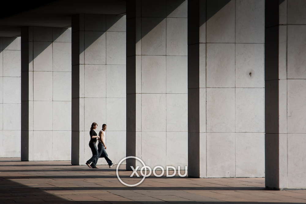 Two people walking through row of white concrete columns (Moskva (Moscow), Russian Federation - Aug. 2008) (Image ID: 080817-1512431a)