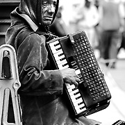 This street accordionist was playing on one of the famous bridges of Paris in St Louis Island in Paris.