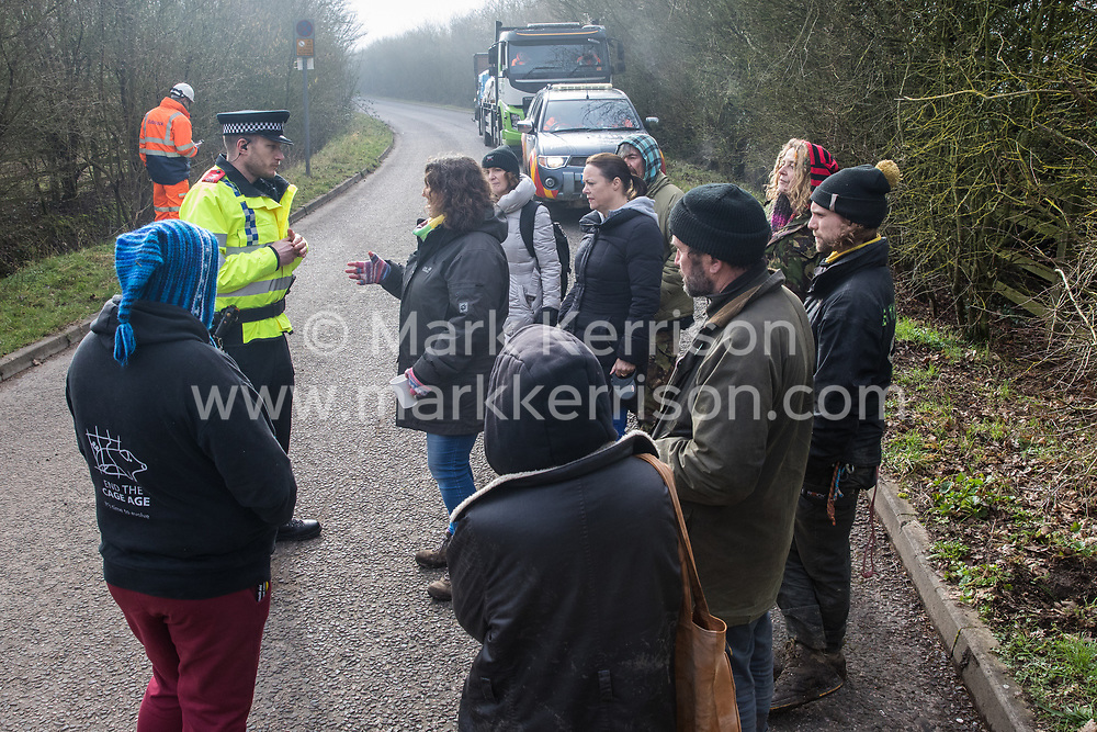 Denham, UK. 6 February, 2020. A police officer speaks to environmental activists from Save the Colne Valley, Stop HS2 and Extinction Rebellion who had been walking at a snail's pace along a road to block a security vehicle and truck delivering fencing and other supplies to be used for works associated with the HS2 high-speed rail link close to the river Colne at Denham Ford. Works planned in the immediate vicinity include the felling of trees and the construction of a Bailey bridge, compounds and fencing, some of which in a wetland nature reserve forming part of a Site of Metropolitan Importance for Nature Conservation (SMI).