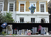 © licensed to London News Pictures. LONDON, UK.  26/07/11. A balloon shaped as a cross floats above the fence of the house. On the day of her funeral fans look at flowers outside the Camden house of Amy Winehouse in North London today (26 July 2011). The singer passed away on Saturday 23th July. Mandatory Credit Stephen Simpson/LNP