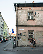 """A couple walks past a mural that says """"I'm happy again"""" in the historic Kazimierz area of Krakow, Poland"""