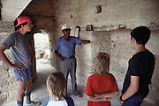 Mayan ruins at Corozal, Belize. A one-armed guide explains the history of the the site to Charles Mann and Sasha Blair and Evan and Jack Menzel. MODEL RELEASED.