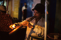 A street vendor smokes a pipe in Ho Chi Minh City, Vietnam.